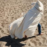 barn der løber med håndklæde på stranden